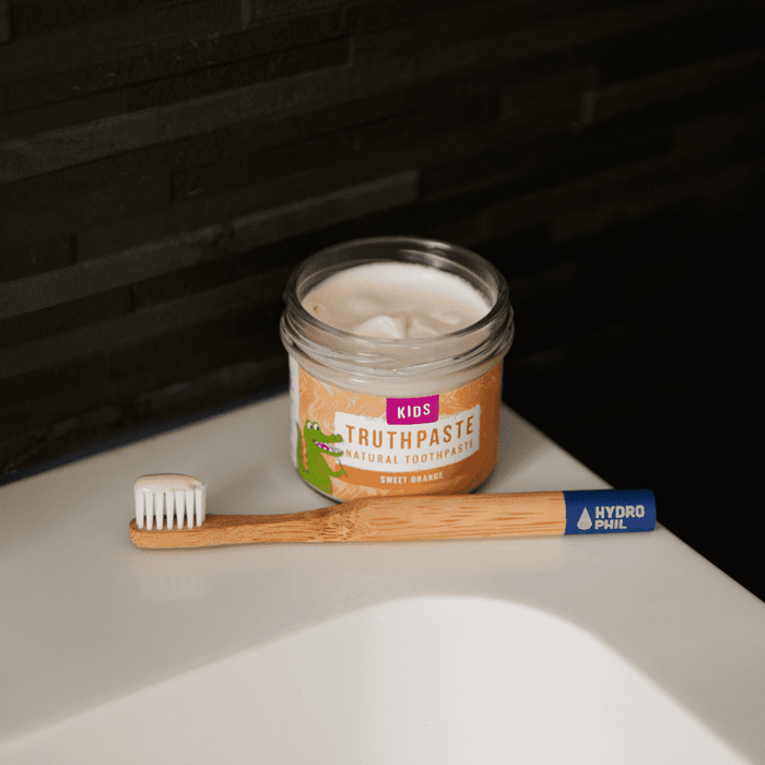 Truthpaste Toothpaste Natural Toothpaste Kids Sweet Orange 120G - Truthpaste on sink with bamboo toothbrush